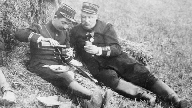 Dos soldados comiendo en el campo, en una foto en blanco y negro