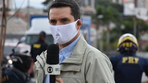 Repórter da Globo de máscara e segurando microfone da emissora em estrada