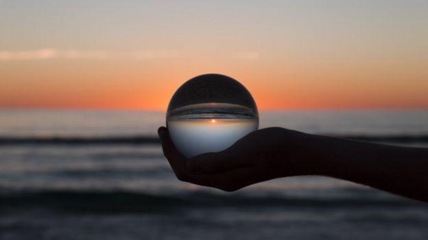 Gün batımı sırasında kumsalda elinde cam küre tutan bir kişi.