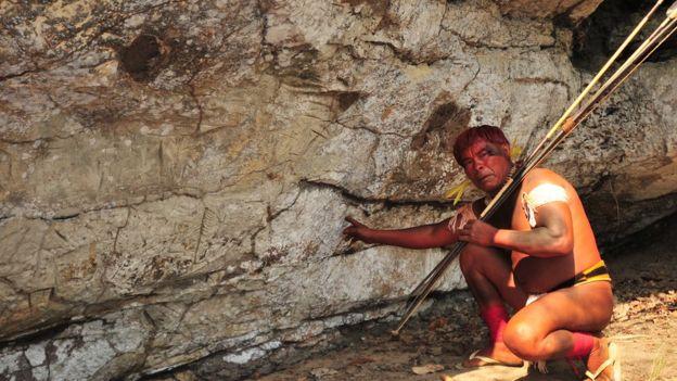 índio waurá mostra gravura na caverna