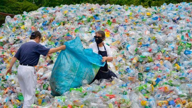 Dos personas rodadas de botellas plásticas.
