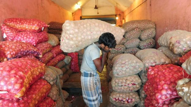 An Indian labourer carries bags of onions into a godown or warehouse at a wholesale market in Chennai on June 1, 2016.