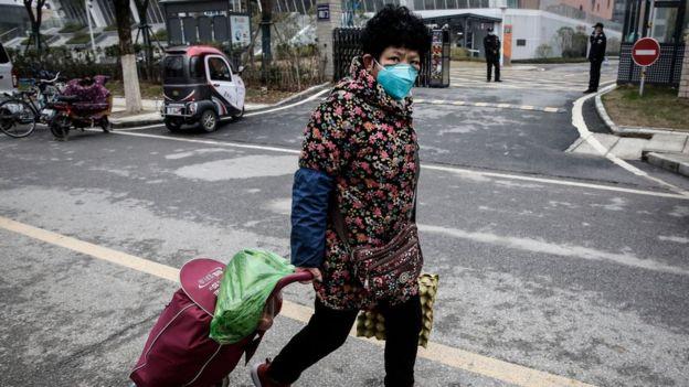 mulher usa máscara em wuhan