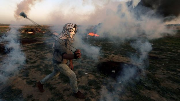 A Palestinian uses a sling to hurl a tear-gas canister during a protest on the Gaza-Israel border fence in the central Gaza Strip on 15 February 2019