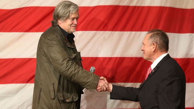 Steve Bannon shakes hands with Roy Moore at an election-eve rally in Alabama.