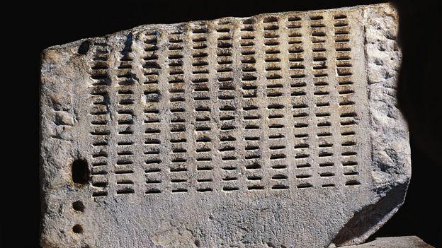 parte de uma kleroterion, uma pedra com diversos buracos no formato de linhas verticais
