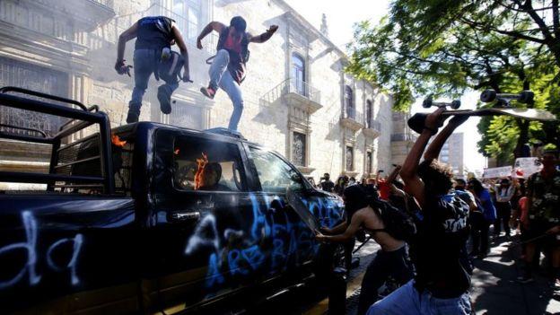 Auto ardiendo durante una protesta en Jalisco, Guadalajara, por la muerte de Giovanni López.