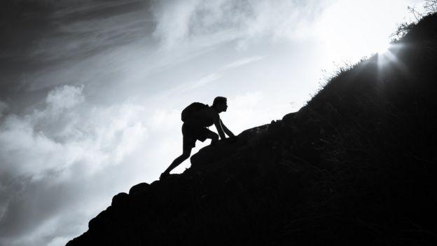Hombre escala montaña.