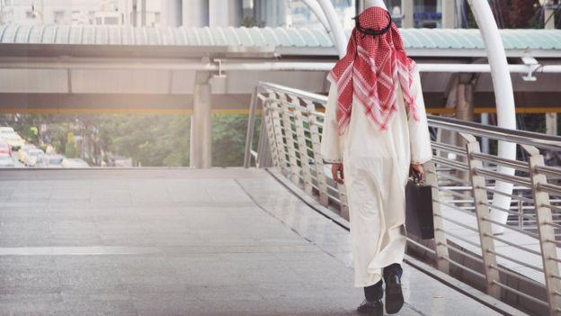 Hombre caminando por un puente.