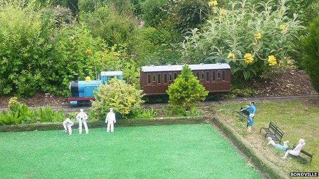 A model train passes figures playing bowls at Bondville