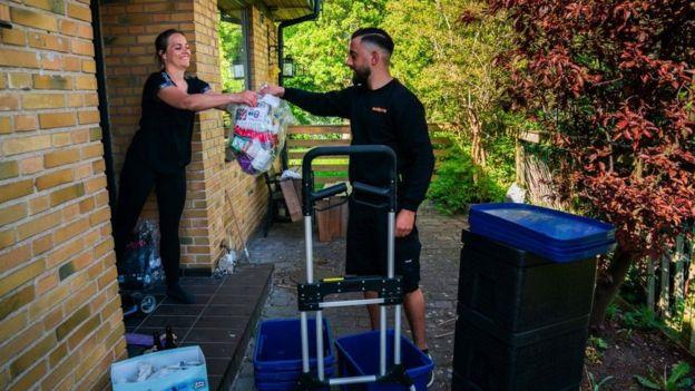 Un empleado entrega un envío en una casa en Suecia.