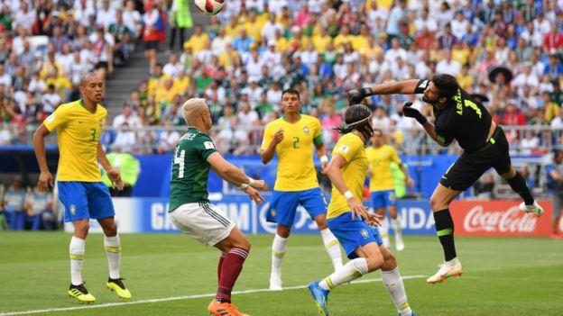 Alisson despeja el centro de Guardado en el primer minuto de partido.