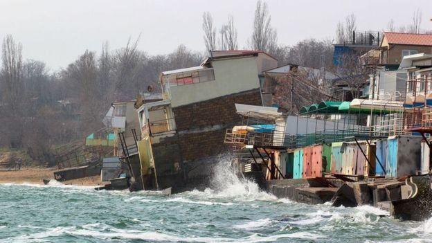Будинки на узбережжі, яке розмивають хвилі