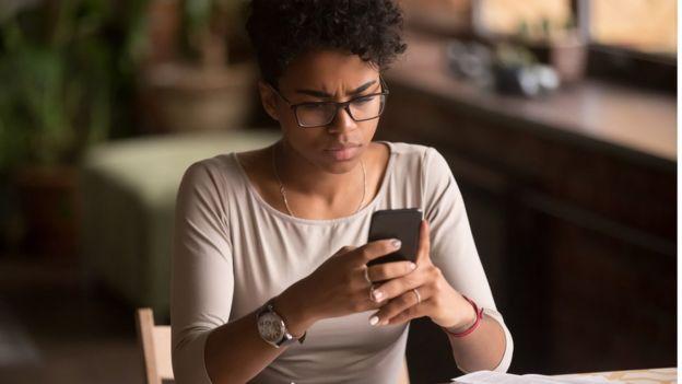 Jovem olha com olhar preocupado algo em seu celular