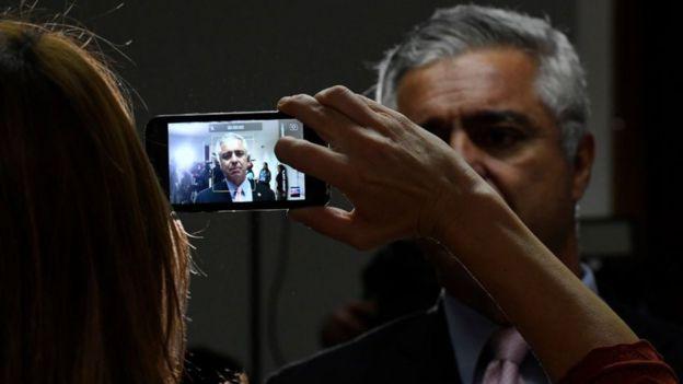 Major Olímpio visto através do visor de um celular enquanto assessora o filma
