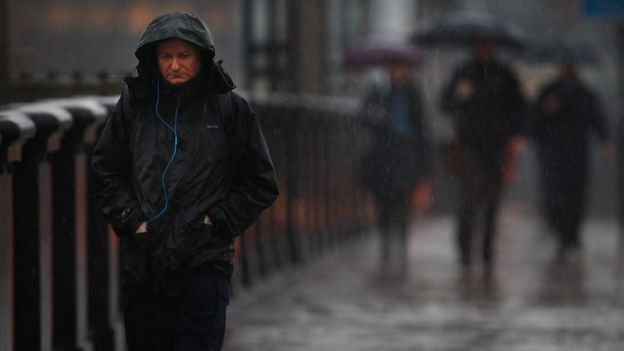 Un hombre caminando bajo la lluvia