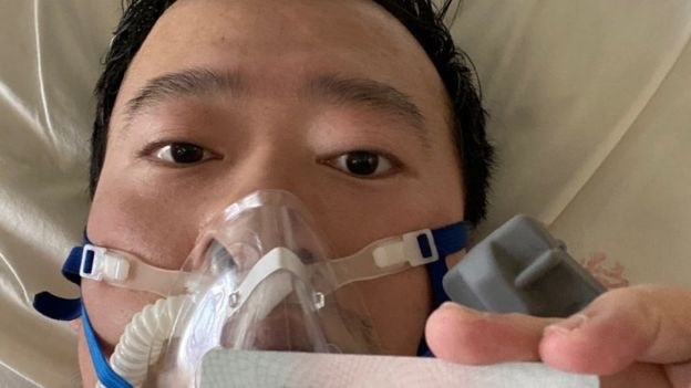 Dr Li shares a picture of himself in a gas mask from his hospital bed in Wuhan on Friday