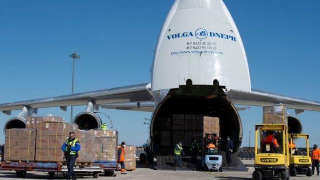 Avião estacionado ao lado de caixas empilhadas e agente do aeroporto francês