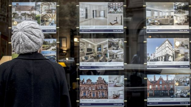 Houses for sale in the window of an estate agents in London