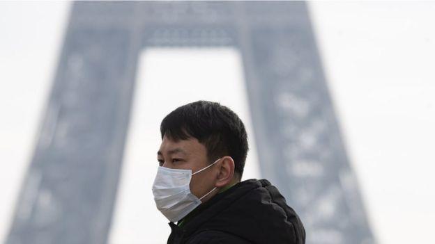 Un turista con una máscara frente a la Torre Eiffel
