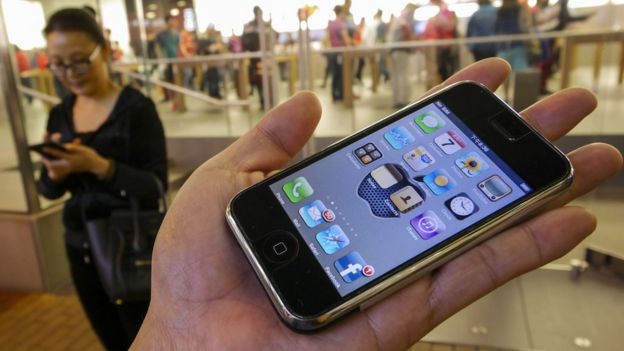 The 1st generation iPhone is held in the palm of a hand outside an Apple store, Hong Kong, 2007