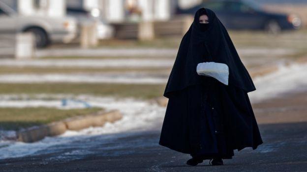 Mulher da comunidade Lev Tahor com sua característica roupa preta