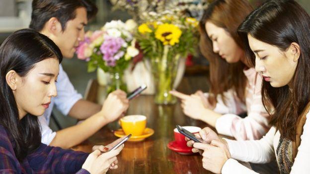 Jóvenes asiáticos mirando sus teléfonos celulares