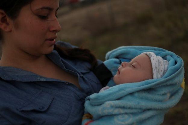 Una mujer guatemalteca sostiene a su bebé después de cruzar la frontera a Estados Unidos.