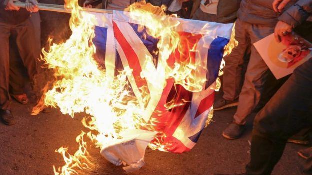 Protesters burn a UK and Israeli flag in Tehran