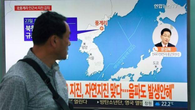 Un hombre camina frente a una pantalla de TV que muestra la posición del sismo en Corea del Norte.