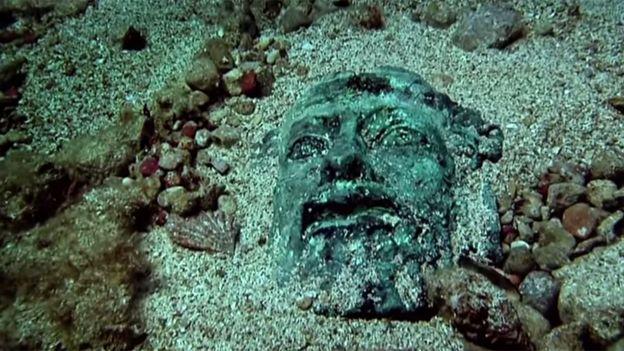Cara de una estatua griega en la arena