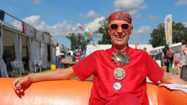 Mae'r artist Andrew Logan o Aberriw yn arddangos ei waith ar faes y Brifwyl // The artist Andrew Logan from Berriew enjoying the sun on a red-hot day