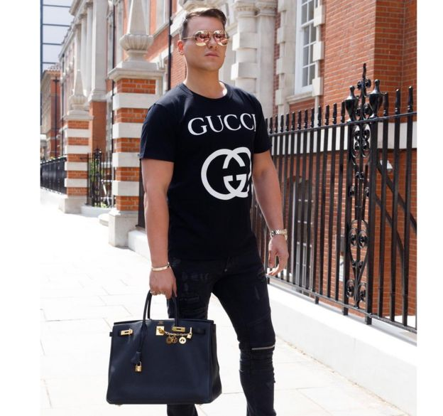 Israel Cassol photographed in the street with a Birkin designer handbag and a Gucci tshirt
