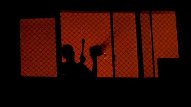 Persona tocando una cacerola en protesta desde una ventana.