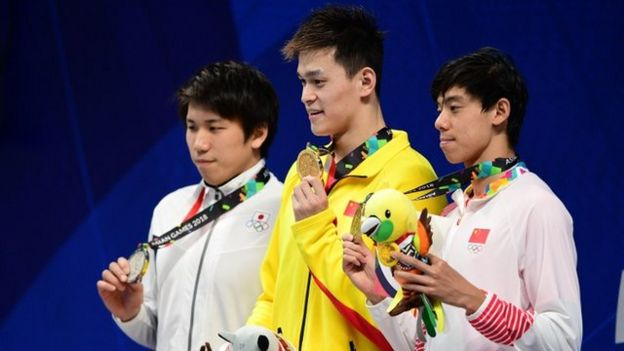 """Silver medallist Japan""""s Katsuhiro Matsumoto, gold medallist China""""s Sun Yang and bronze medallist China""""s Ji Xinjie celebrate during the victory ceremony of the men""""s 200m freestyle swimming event during the 2018 Asian Games in Jakarta on August 19, 2018."""