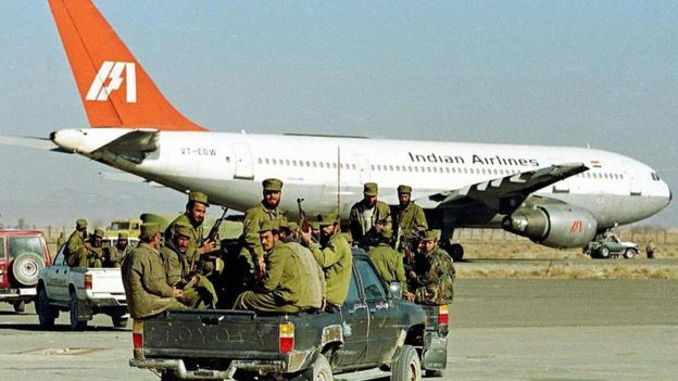 Taliban Islamic militia commandos ride in the rear of a truck towards an aircraft of Indian Airlines hijacked by Islamic Kashmiri militants