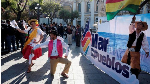 """Bolivianos bailan frente a un cartel en el que se lee: """"Mar para los pueblos""""."""