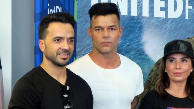 Puerto Rican singers Luis Fonsi (L) and Ricky Martin (C), accompained by well-being and of the health activist , Laura Posada (R), attend a press conference at the Luis Munoz Marin International airport in San Juan, Puerto Rico, 02 October 2017.