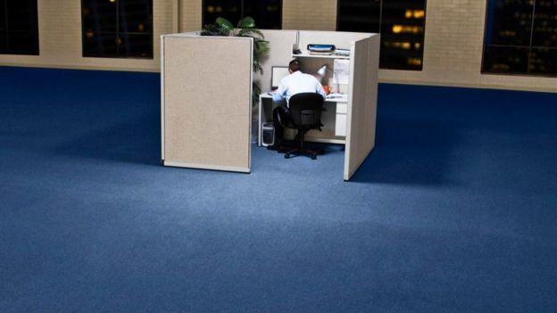 Una persona en un cubículo solitario en una oficina vacía