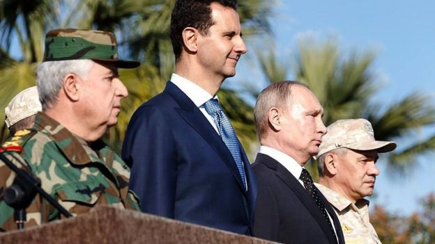 Syrian President Bashar al-Assad (2nd Left) and Russian President Vladimir Putin (2nd Right) stand beside each other at Russia's Hmeimim airbase near Latakia, Syria