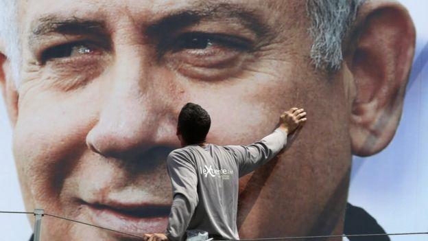 عامل يثبت صورة إعلانية لنتنياهو خلال الحملة الانتخابية الأخيرة