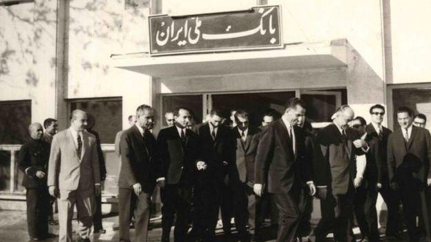 یوسف خوش کوش (نفر پنجم از راست که دستش را بالا گرفته) به همراه جمشید آموزگار در حال خروج از بانک ملی ایران. آقای خوش کوش در زمان نخست وزیر جمشید آموزگار به ریاست کل بانک مرکزی منصوب شد