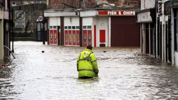A man wades through floodwater in a street in Dumfries