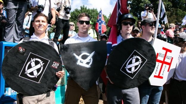 White nationalists hold shields with symbols on