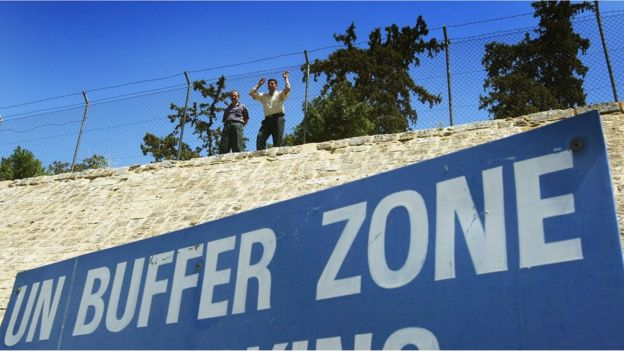Turkish Cypriots look over the UN Buffer Zone into the Greek part of the divided city of Nicosia from the Turkish side on 25 April, 2004