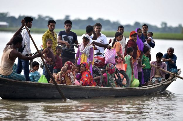 Villagers in Assam travel by boat during floods in 2016