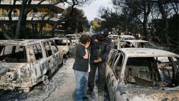 Bombeiro atende mulher em meio a veículos queimados