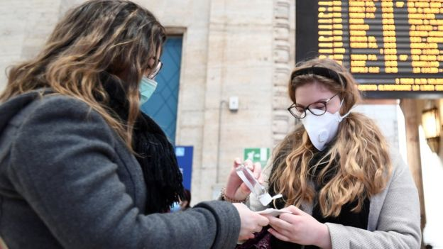 Women wearing face masks disinfecting their hands at a railway station in Milan, 24 Feb 2020