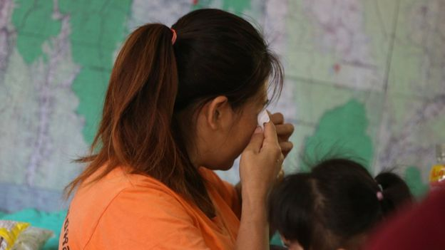 A relative of the 12 boys and their soccer coach trapped in the Tham Luang cave complex cries while listening to a news conference about the death of a Thai rescue diver