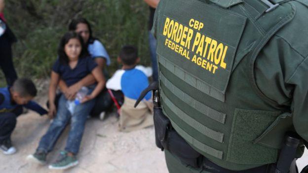 Agente de fronteira com imigrantes